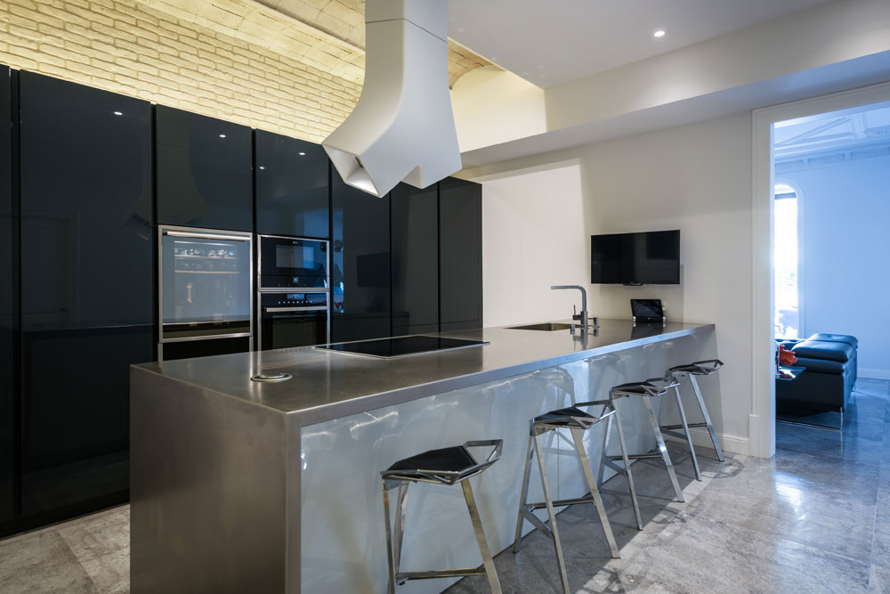 piso Ensanche Barcelona diseño de SINCRO. Cocina con peninsula de acero inoxidable. Campana de isla YE de Elica